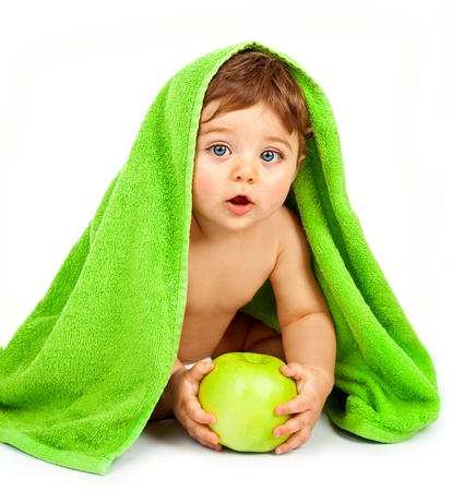 a cute little boy eating big fresh apple, adorable child covered green towel isolated on white background, closeup portrait of cheerful kid enjoying healthy nutrition, health care concept   photo