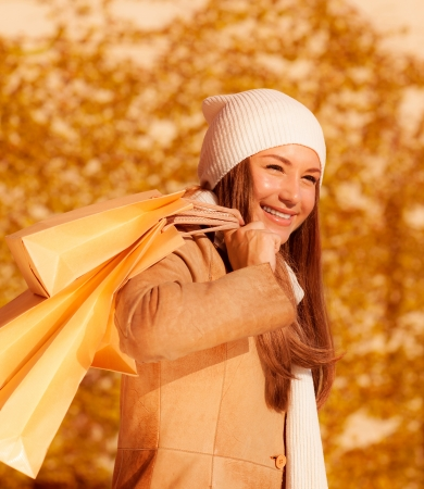 a beautiful girl with shopping bag, closeup portrait of attractive female isolated on autumn foliage background, young lady enjoying her purchase, autumnal sales, spending money  photo
