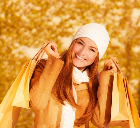 gift spending: Image of attractive cheerful woman with brown shopping bags on golden autumn background, closeup portrait of happy female enjoying gift bags, spending money concept, sales season    Stock Photo