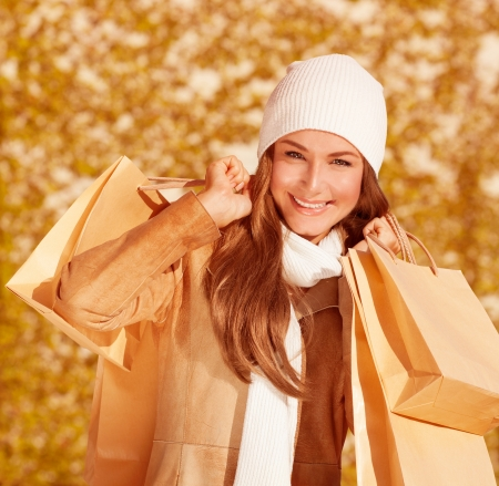 Image of beautiful happy female holding brown paper bag in hands, closeup portrait of cute cheerful young lady wearing stylish coat and white hat and scarf, woman having fun outdoors  photo