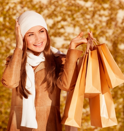 a fashionable woman hold golden presents bag on yellow autumnal background, closeup portrait of cute stylish girl having fun outdoors, autumn seasonal sale, spend money concept
