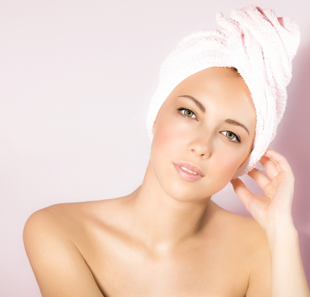 a beautiful girl in spa salon, closeup portrait of attractive woman isolated on pink background, cute female enjoying day spa, young pretty lady with bath towel on head, beauty treatment   photo