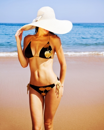 a sexy woman on the beach, attractive female wearing black seductive swimsuit and big fashionable hat, healthy slim girl stand on coastline, summer holidays, luxury resort, vacation concept  photo