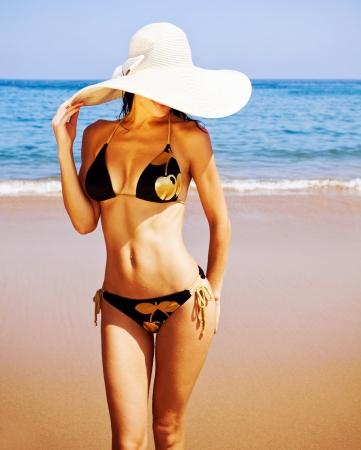 eine sexy Frau am Strand, attraktive Frau mit schwarzen verführerische Badeanzug und großen modischen Hut, gesunde schlanke Mädchen stehen auf Küste, Sommerferien, Luxus-Resort, Urlaub Konzept