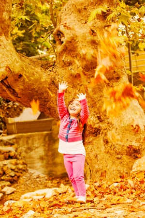 Picture of little cute girl play in autumn park, adorable sweet kid throwing up old dry leaves and laughing, nice small female child enjoy fall nature, seasonal falling leaf, happiness concept  photo