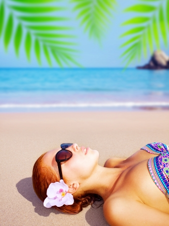 Picture of young beautiful lady on the beach, attractive female enjoying dayspa on seashore in luxury spa resort, sexy girl with orchid flower in red hair lying down on ocean coastline  photo