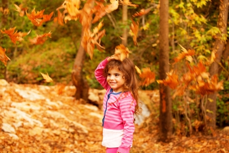 a sweet little girl in autumn forest, adorable child playing game in fall park, pretty kid enjoying autumnal nature, beautiful golden trees foliage, nice warm sunny day  photo