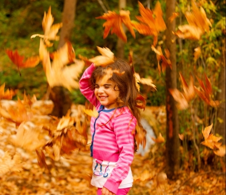 a little cute girl playing in autumn park, adorable sweet kid throwing up old dry foliage, cheerful small female child playing outdoors, nice toddler laughing with closed eyes  photo