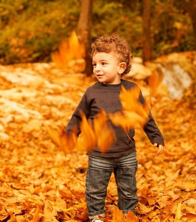 a cheerful small kid having fun outdoors, adorable toddler play game on backyard, nice curly little boy enjoying walk in autumn park, beautiful autumn season, happy childhood   photo