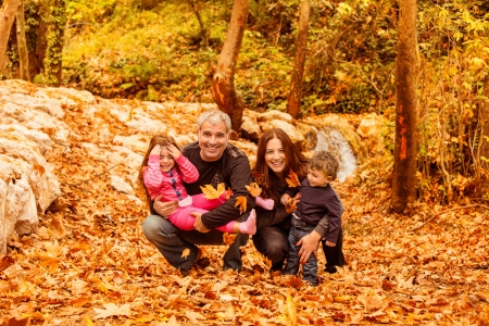 happy family concept: Image of beautiful female and man with cute daughter and pretty son having fun in autumnal forest, young parents with nice adorable kids playing outdoor, fall holiday, happy family concept