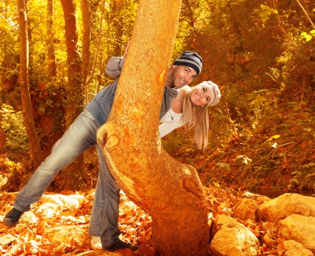 a happy couple playing love game in autumn park, portrait of two loving people peeking from behind a tree, young family spending time together outdoors, relationship and happiness concept   photo