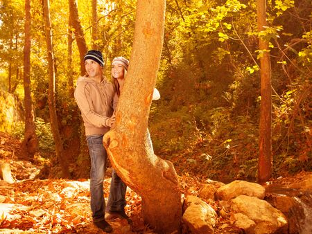 Picture of happy pretty youth enjoying beautiful autumn woods, cute woman and handsome guy wearing stylish warm hats, young family hugging in fall park, romantic relationship, love concept Stock Photo - 15871501