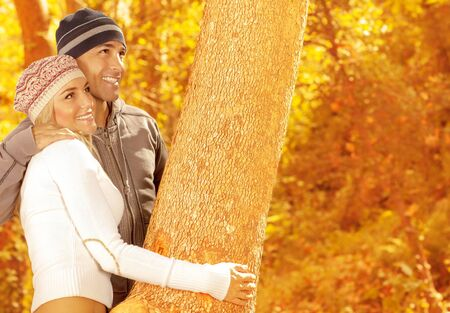 a of happy couple playing game in autumn park, closeup portrait of two loving people hugging tree, cute woman and handsome guy wearing stylish warm hats, happiness and affection concept   Stock Photo - 15871493