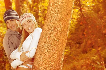 Picture of two happy people spending time together in beautiful autumn woods, closeup portrait of attractive female with handsome male standing near tree over golden trees foliage 
