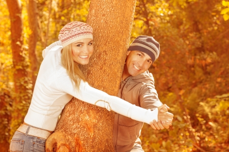 Image of cheerful couple playing around tree in autumnal park, happy young family having fun in autumn garden, sweet teenagers dating in fall woods, romantic relationship, love concept  photo