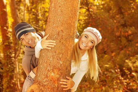 Photo of happy young family having fun in autumnal woods, closeup portrait of cute cheerful couple peeking from behind a tree outdoors, beautiful golden autumn season, love concept Stock Photo - 15871489