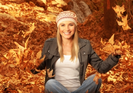 Picture of happy blonde girl having fun in autumn woods, pretty woman throwing up dry autumnal leaves in the forest, beautiful female sitting down on ground covered golden foliage    photo