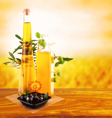Picture of olive oil still life on wooden table over sunset, glass jar with oil and fresh olives vegetables on yellow gardening background, italian salad dressing, healthy nutrition concept   photo