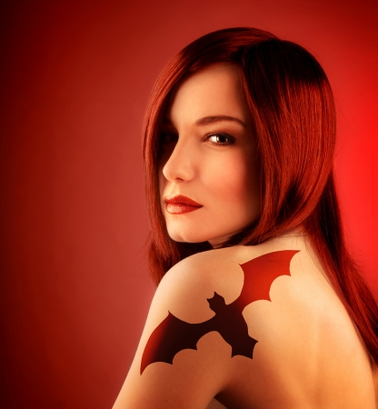 tatoo: a beautiful sexy girl with bat tattoo on shoulder isolated on red background, Halloween holiday decoration, seductive female with red hair, attractive dangerous witch