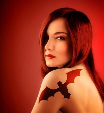 brujas sexis: una hermosa chica sexy con tatuaje bate en el hombro aislado sobre fondo rojo, la decoración fiesta de Halloween, mujer seductora con el pelo rojo, bruja peligroso atractivo