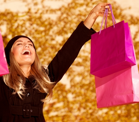 people laughing: an attractive woman expressing joy of her new purchase, happy good looking girl with pink shopping bags walking in autumn park, money spending and  anti stress concept, autumnal sale