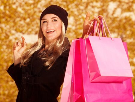 Shoping: Picture of shopper girl holding presents bags in hand, beautiful customer enjoy autumnal season sales, closeup portrait of cheerful woman with shopping bag isolated on fall foliage background