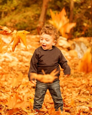 Image of lovely boy enjoying falling leaves in dry orange woods, sweet child laughing in autumn garden, little toddler standing in beautiful fall park, carefree childhood, happines concept  photo