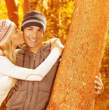Picture of happy family spending fun time together in beautiful autumn park, closeup portrait of husband and wife kissing, young adult couple enjoying outdoor, love and joy concept Stock Photo - 16010532
