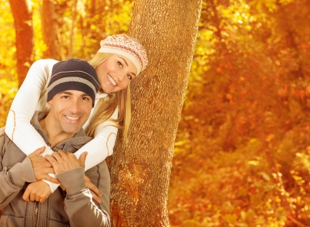 Picture of two happy lovers having fun in autumn forest, pretty blond girlfriend with handsome boyfriend playing in autumnal woods, young beautiful woman cuddling nice guy, love and happiness concept photo