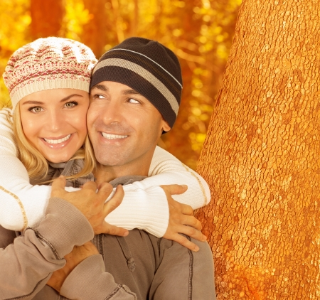 Image of happy young family relaxed in autumnal backyard, first romantic dating, closeup portrait of beautiful smiling couple wearing warm stylish hats, romance lifestyle, autumn season, love concept Stock Photo - 16010566