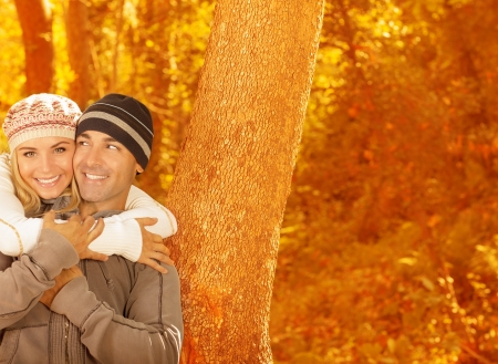 Photo of happy couple hugging each other in autumn park, two cheerful lovers having fun in autumnal forest, young family relaxed in autumnal backyard, first romantic dating, love and happiness concept Stock Photo - 16010539