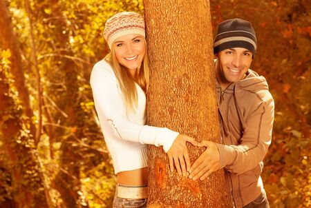 Picture of two happy people having fun in autumnal forest, beautiful lovers hugging tree in fall park, boyfriend and girlfriend making heart shape by hands, romantic relationship, love concept photo