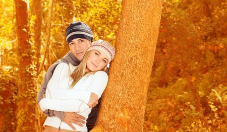Picture of loving couple standing and hugging near tree in autumnal forest, romantic relationship, leisure time, fall season, autumn vacation, enjoying nature, love concept Stock Photo - 16010523