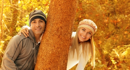 Photo of happy couple enjoying autumn nature in the park, boyfriend and girlfriend playing game outdoors, young family having fun in fall forest, smiling pair hugging tree, warm weather Stock Photo - 16010616