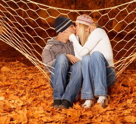 Picture of loving pair swinging in hammock and kissing, romantic relationship, happy family concept, wife and husband hugging in fall park, beautiful autumn season, orange foliage under feet photo