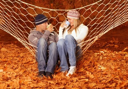 Image of beautiful young couple sitting in hammock and drink hot chokolate, lovely woman with handsome man relaxed outdoors on backyard garden, golden autumn season, yellow autumnal forest photo