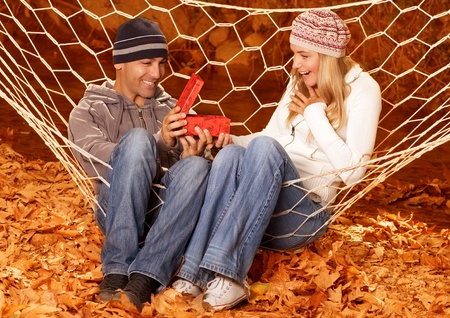 Photo of happy girl received gift for birthday from her boyfriend, handsome husband give present box for his lovely wife, couple in hammock in autumn forest, autumnal park, fall season photo