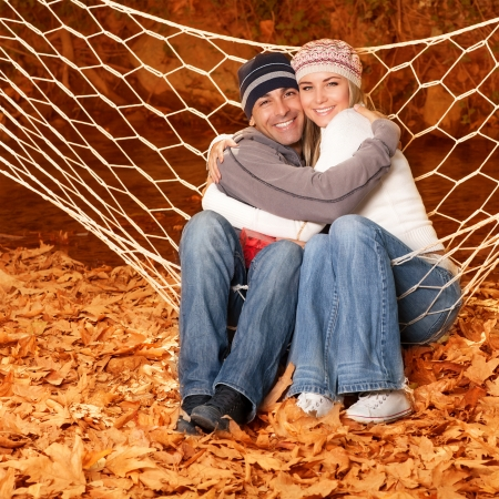 Picture of happy young family hugging in autumnal park, cheerful smiling couple swinging in hammock on backyard, pretty blond woman and cute man enjoying autumn nature in the woods Stock Photo - 16010530