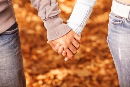 mani e piedi: Foto di due persone che amano tenendosi per mano su sfondo dorato autunnale, relazione romantica, migliori amici, coppia felice, caduta di fogliame arancione sotto i piedi, la felicit� e il concetto d'amore