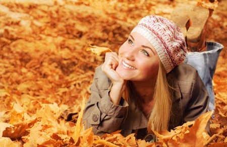 Image of cheerful teen laying down on the ground covered dry autumnal foliage in beautiful park photo