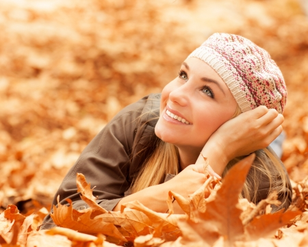 Picture of attractive female laying down on the ground covered dry autumnal foliage in beautiful park photo