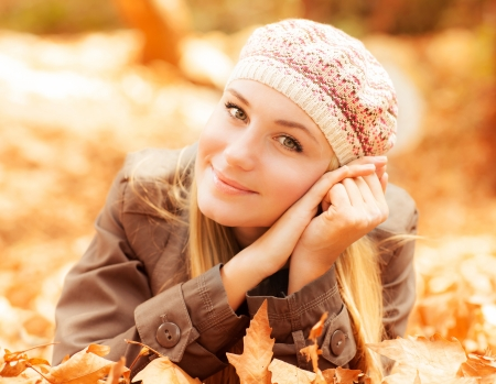 lying in leaves: Photo of cute girl laying down on the ground covered dry autumnal foliage in beautiful park in sunny day Stock Photo