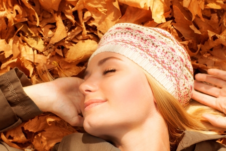 Picture of pretty woman sleeping outdoors, cute female laying down on autumnal foliage with closed eyes, pleasure expression on face of young woman, autumn park, leisure time, joy concept photo