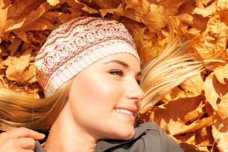 laying down: Image of pretty female laying down on old dry tree leaves, cute blond teenager having fun outdoors, attractive woman wearing warn beret, leisure time, relaxation outside, autumn season, sunny day