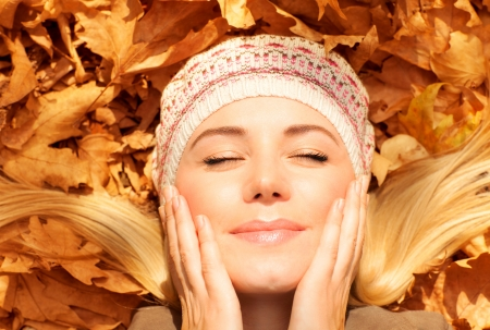 Picture of pretty woman laying down on the ground covered golden autumnal foliage with closed eyes photo