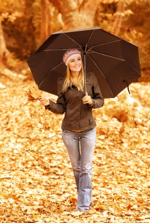 Photo of cute girl walk with stylish black umbrella in the autumn park, pretty woman walking outdoors in rainy weather and holding bouquet of autumnal leaves in hand, fall season, youth lifestyle  photo