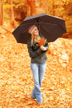 Picture of pretty woman standing under umbrella in fall forest in rainy weather, happy smiling blond girl in stylish beret walking in autumnal park, enjoying nature, autumn weekend, raining outdoors Stock Photo - 16010578