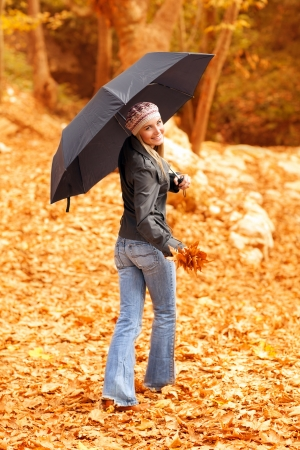 fall fun: Image of attractive young lady standing under black umbrella in autumn forest in rainy weather, active healthy woman wearing colorful warm hat, nice blond girl holding dry autumnal leaves in hand