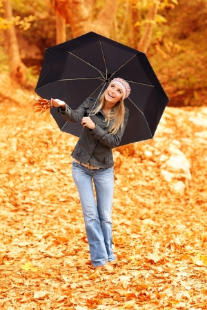 Photo of beautiful female standing under umbrella, cute woman peek out from under the black stylish parasol, rainy weather, autumnal park, fall forest, autumn season, fun and joy concept Stock Photo - 16010583