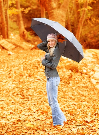 Photo of lovely woman walk under umbrella in rainy day in autumnal park, cute female holding dry tree leaves in hand, sweet girl standing with black stylish parasol in fall woods, autumn season photo